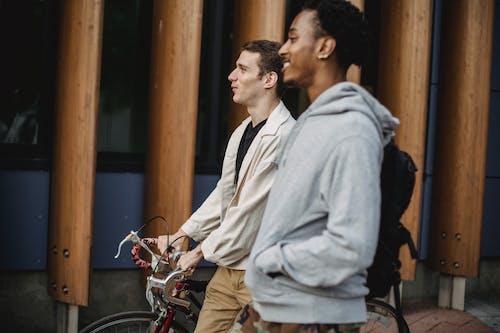 Positive diverse friends with bike walking on street