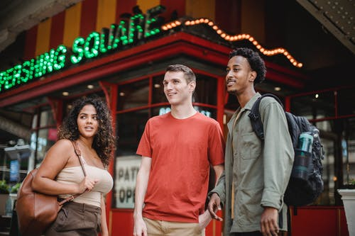 Group of young multiracial friends in casual outfits with backpacks standing in city street near building with sign and looking away in daytime