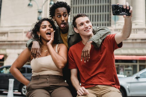 Positive young multiethnic friends in casual clothes taking selfie on phone while making funny faces in city street