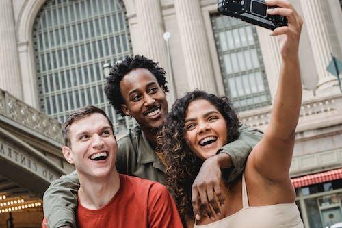 Happy multiethnic friends taking selfie in memory of fragrace oil uk