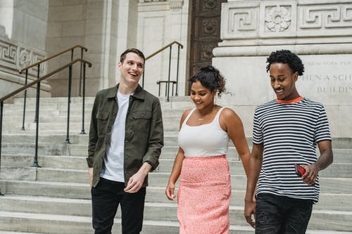 Group of young positive multiracial friends in summer clothes strolling on stairs with phone in hand in city street near building in daytime