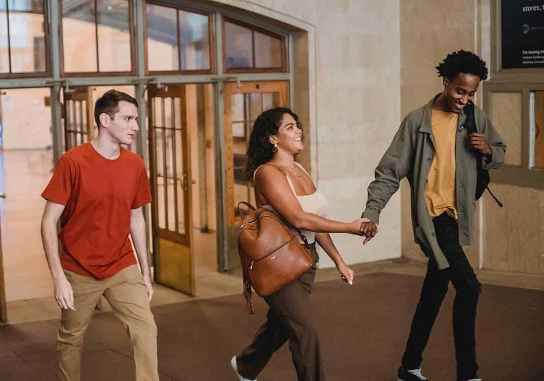 Happy young multiethnic couple together with male friend leaving university