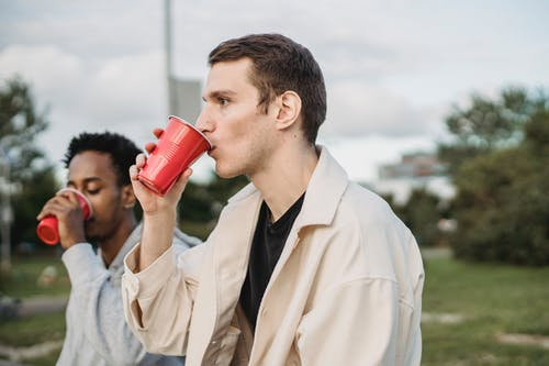 Young multiethnic friends enjoying takeaway beverages in park