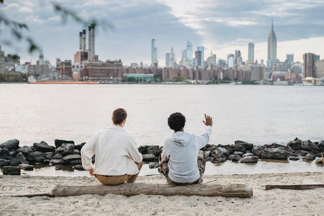 Back view of crop anonymous multiracial friends sitting together on wooden trunk on bank of river and looking at urban landscape