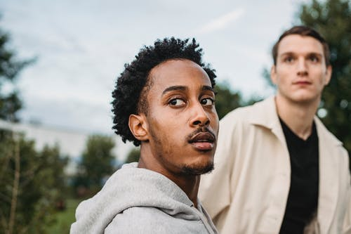 Serious black man looking over shoulder together with male friend