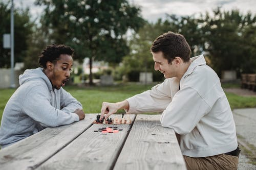 Side view of smiling young multiracial male friends sitting at wooden table in city park and enjoying interesting chess game