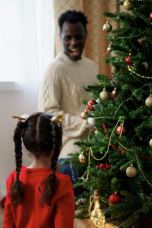 Girl in Red Sweater Standing Beside a Christmas Tree