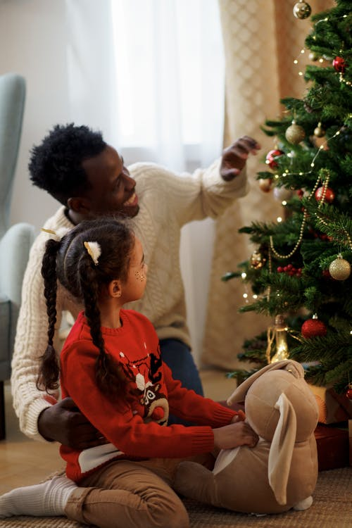 Dad and Daughter Sitting on Floor While Looking at a Christmas Tree