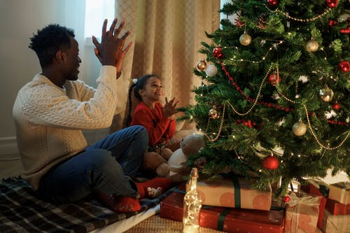 Dad and Daughter Sitting and Clapping Near a Christmas Tree