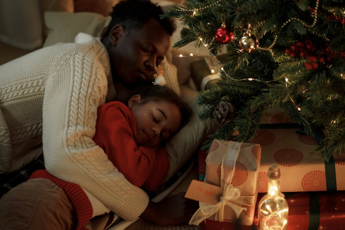 Dad and Daughter Lying Down Near a Christmas Tree