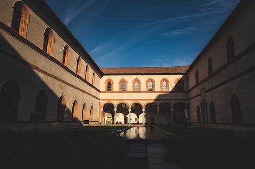 Garden in Ducal Courtyard of historic Castello Sforzesco with arched windows and passage against bright blue sky in Milan