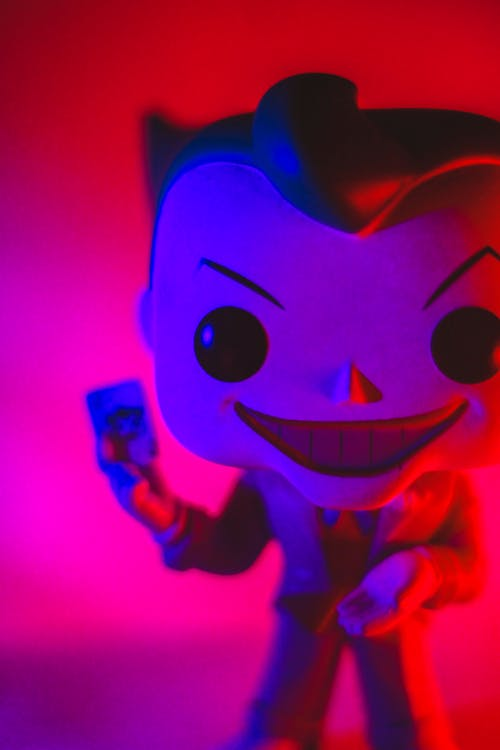 Little extraordinary toy of superhero with angry big smile in bright light on blurred background