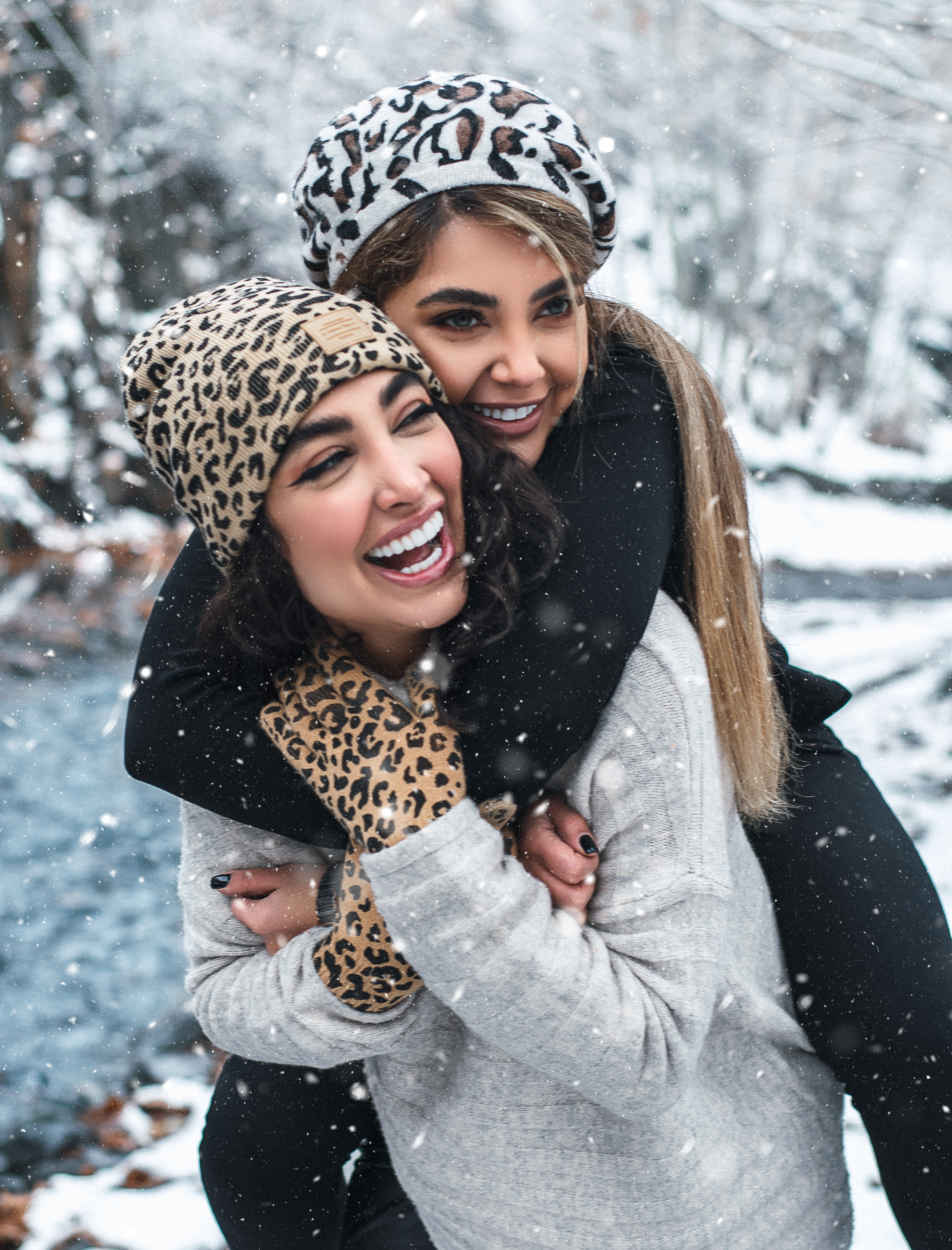 laughing woman carrying girlfriend on back in winter forest