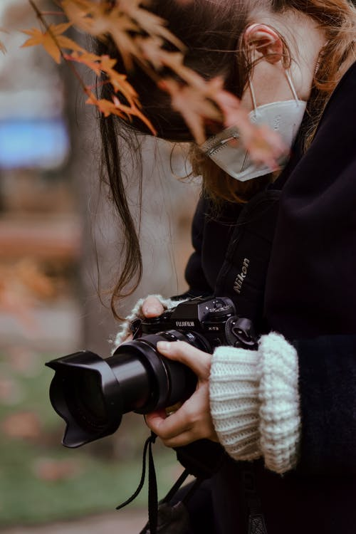 Side view of young woman in warm clothes wearing facial mask standing in park and taking pictures on professional camera on autumn day