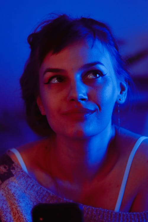 Thoughtful woman looking up in room with neon light