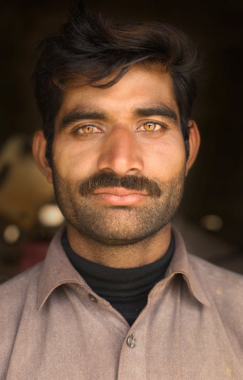 Serious unshaven Indian man with mustache and brown eyes and dark hair looking at camera