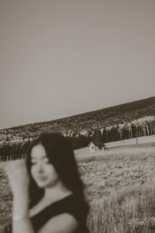 Wanita Berkemeja Hitam Berdiri Di Lapangan Rumput