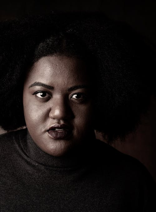 Grayscale Photo of an Afro-Haired Woman in Turtleneck Sleeves