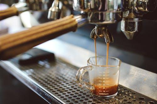 Professional coffee machine brewing coffee in glass