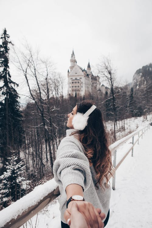 A Woman in Gray Knit Sweater Standing Snow Covered Railings Across the Neuschwanstein Castle