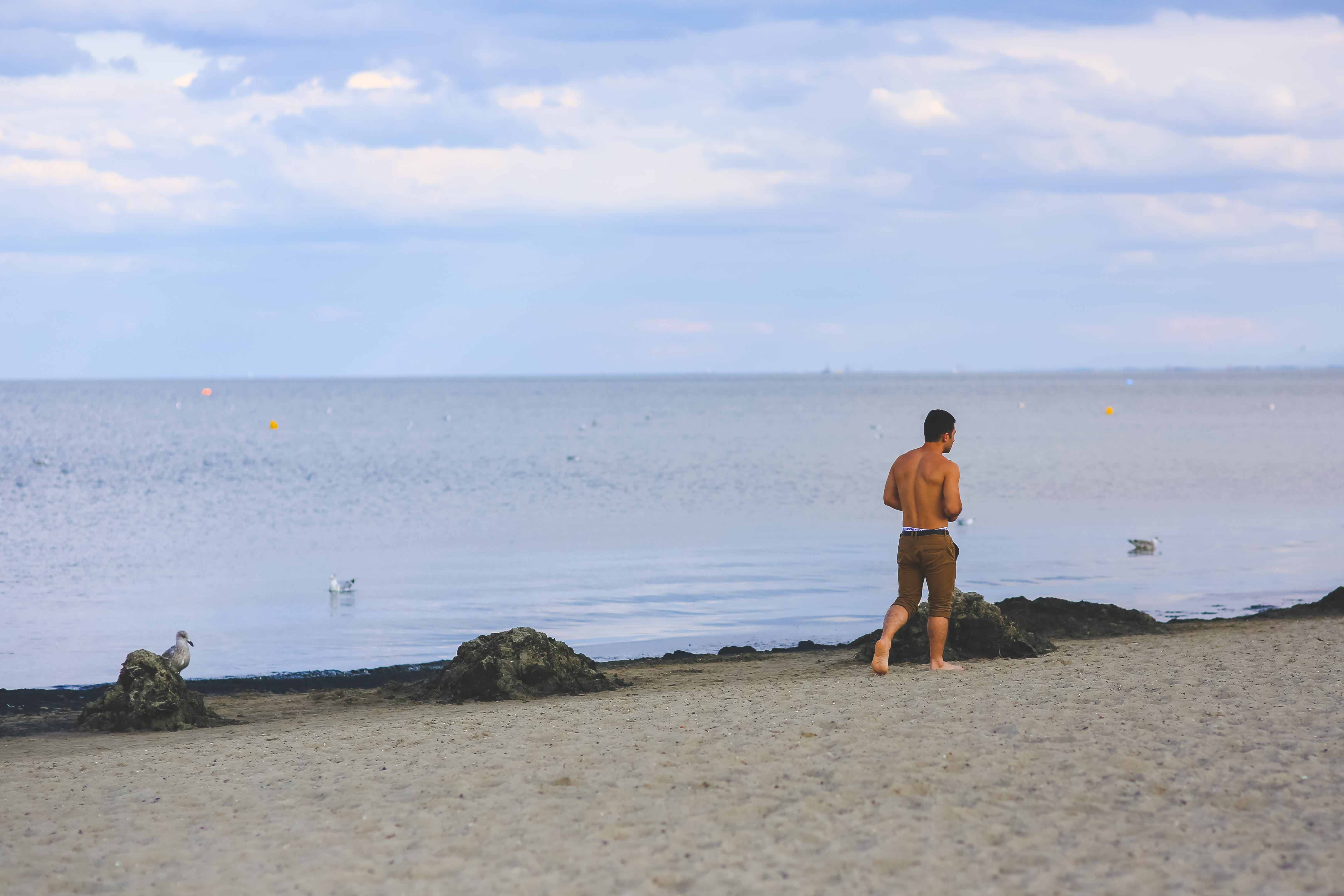 Young man walking on sand beach