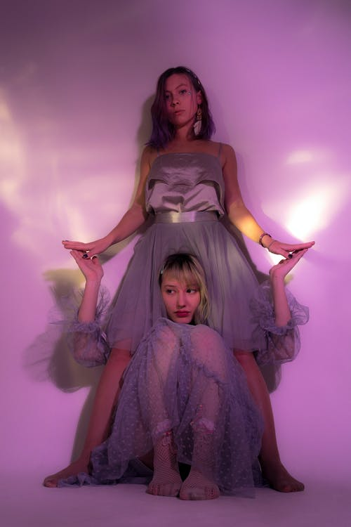 Full body of woman sitting between legs of female friend and touching hands in studio with purple illumination and light glare in studio