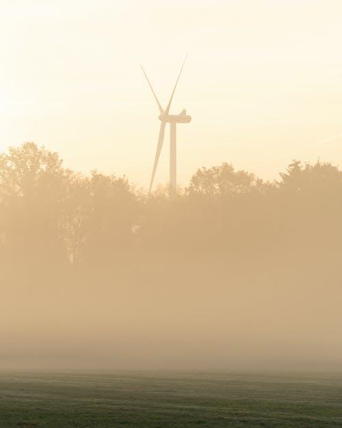 White Wind Turbine on Green Grass Field during Sunset