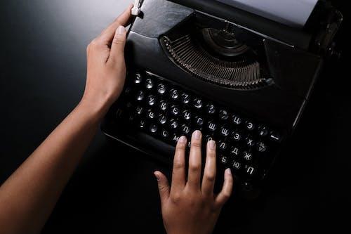 黒いテーブルに黒いタイプライターを持っている人