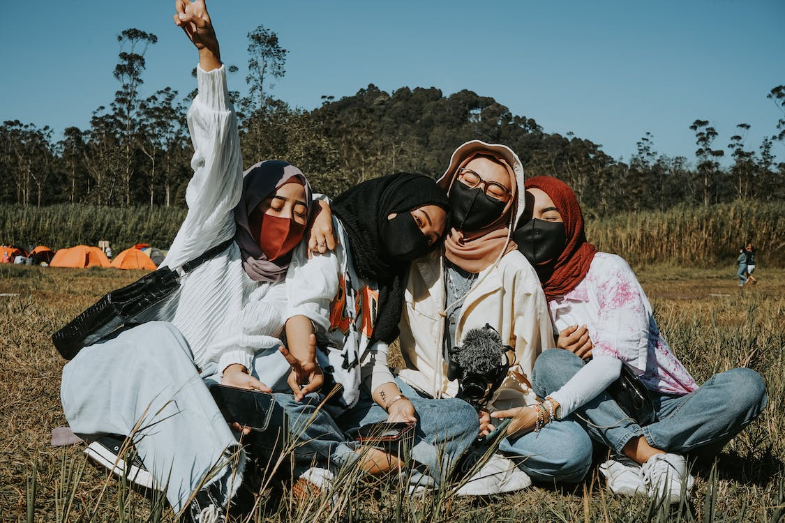 Group of Muslim women in protective masks and casual outfits sitting close on lawn during coronavirus pandemic