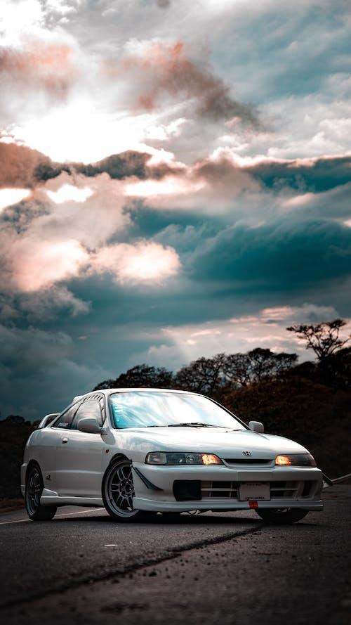White Sedan on Brown Field Under Gray Clouds