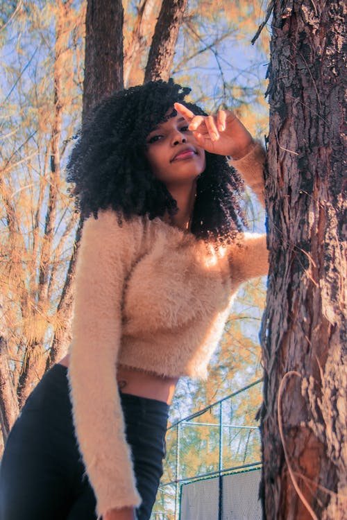 Black woman leaning on tree trunk while spending time in urban park