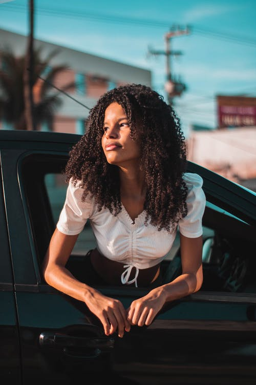 Confident young African American woman wearing elegant white blouse hanging out window of modern black car on urban street in sunlight