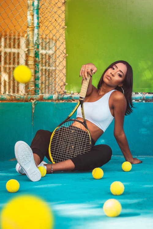 Confident young ethnic woman sitting on tennis court with racket among yellow balls