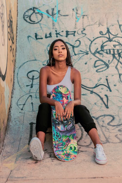 Positive young black woman sitting on hand painted ramp with colorful skateboard