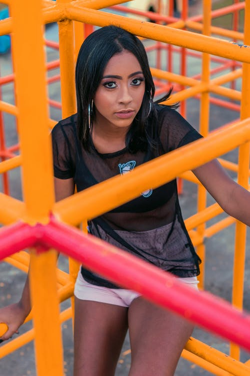 From above of carefree African American female wearing transparent t shirt and shorts sitting in colorful metal maze and looking at camera