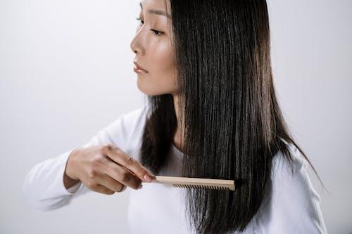 Woman in White Long Sleeve Shirt Holding White Pen
