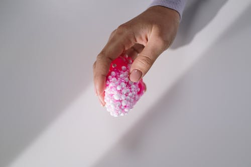 Person Holding Pink and White Beads