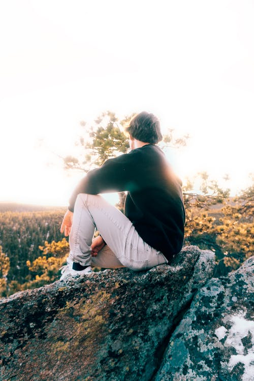 Man in Black Tank Top and White Pants Sitting on Rock