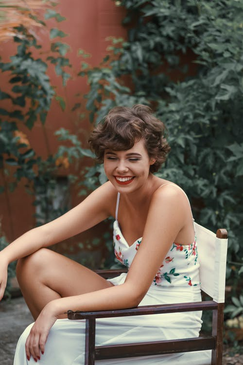 Woman in White and Green Floral Spaghetti Strap Dress Sitting on Brown Wooden Bench