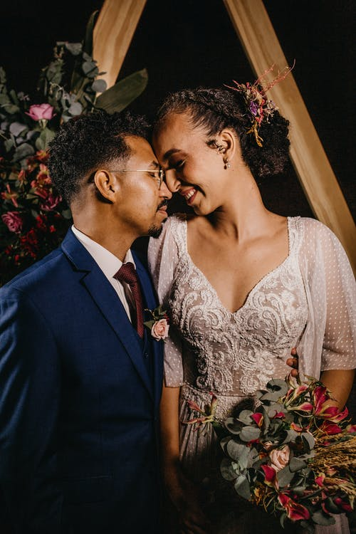 Smiling diverse couple with flower bouquet after getting married