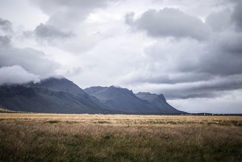 Brown Grass Field and Gray Mountains Under Gray Clouds