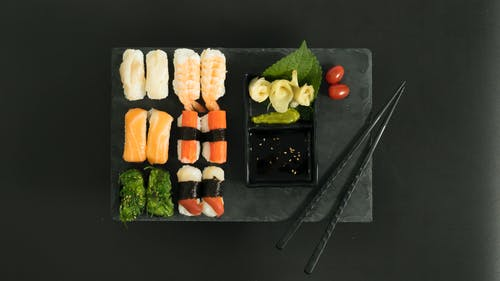 Sliced Carrots and Green Vegetable on Black Rectangular Tray