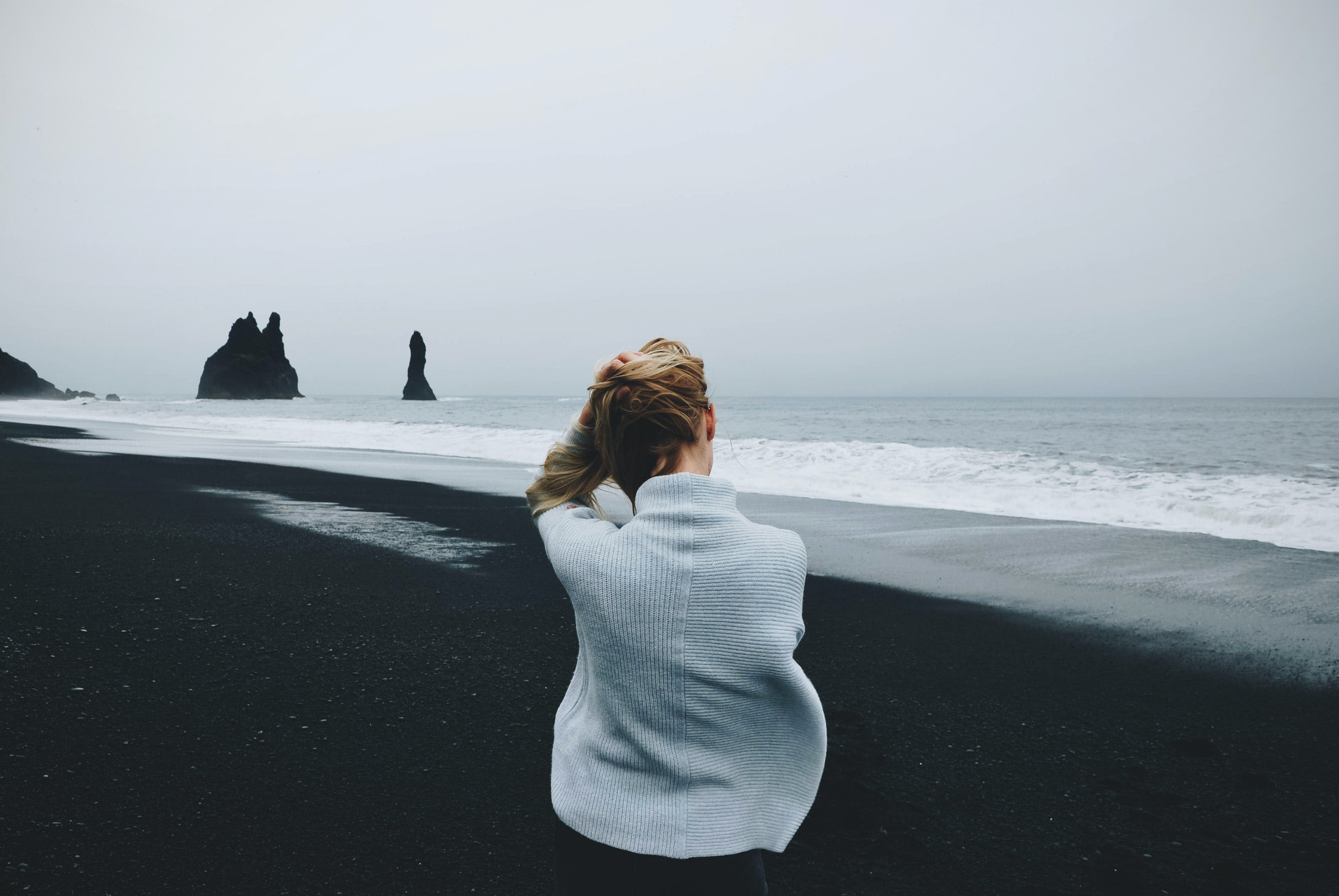 Woman Wearing Sweater Standing in Front of Beach