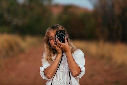 Ilmainen kuvapankkikuva tunnisteilla blondi, epäselvä tausta, kamera