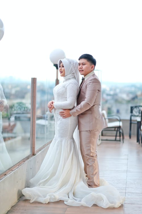 Young Asian just married couple enjoying cityscape standing on balcony of big building