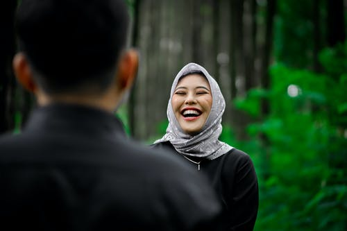 Woman in White Hijab Standing Beside Man in Black Long Sleeve Shirt