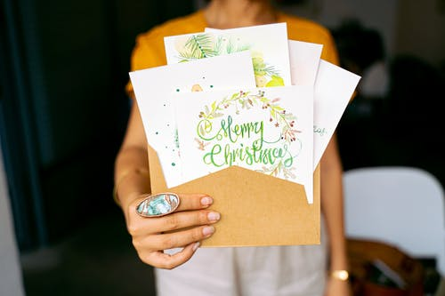 Person Holding Brown and Green Greeting Card