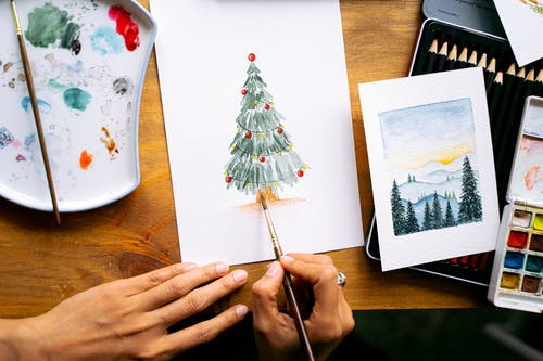Person Holding Green and White Christmas Tree Drawing
