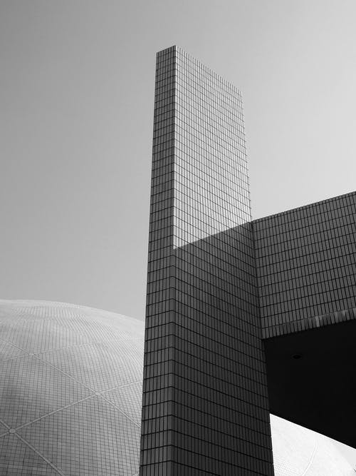 Low angle black and white of contemporary high geometric exterior of glass skyscraper in daytime under sky