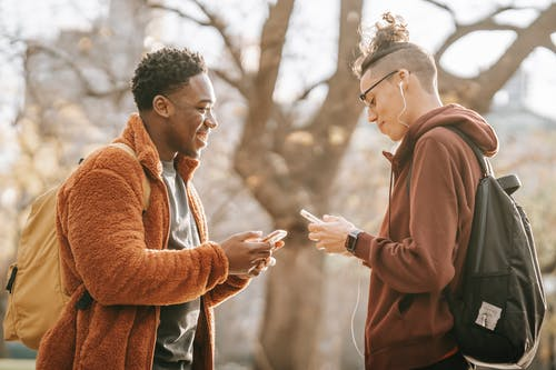 Side view of smiling young multiracial male friends wearing warm clothing standing opposite each other and  browsing cellphones on blurred background